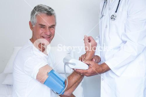 Doctor checking senior mans blood pressure
