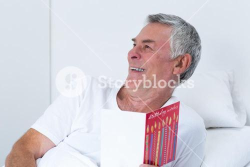 Senior man holding birthday greeting card