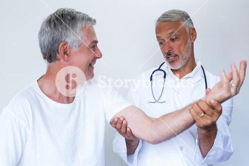 Male doctor giving palm acupressure treatment to senior man