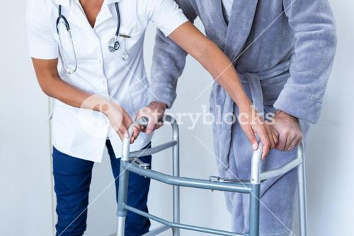 Mid-section of female doctor helping senior man to walk with walker