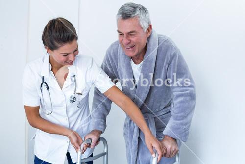 Female doctor helping senior man to walk with walker