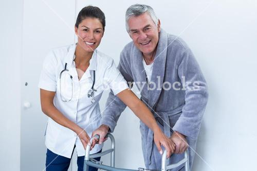 Portrait of female doctor helping senior man to walk with walker
