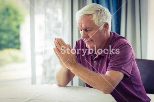 Senior man praying in living room