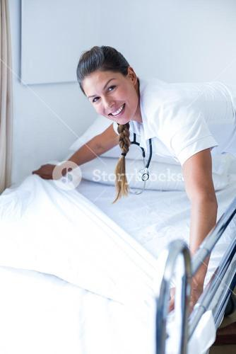 Portrait of smiling female doctor preparing the bed