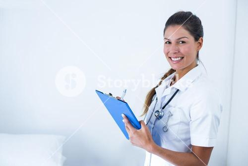 Portrait of female doctor writing on clipboard in hospital