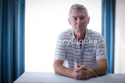 Portrait of confident senior man in living room