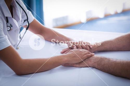 Mid section of female doctor consoling senior man in living room