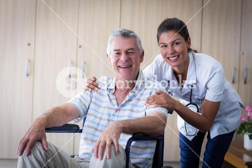Portrait of smiling senior man and female doctor in living room