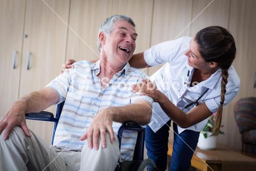 Happy senior man and doctor interacting in living room