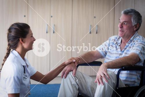 Female doctor consoling senior man in living room