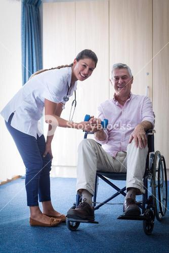 Portrait of female doctor assisting senior man in lifting dumbbell