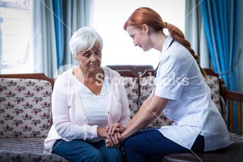 Female doctor consoling senior woman in living room