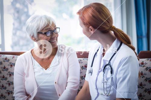 Senior woman and female doctor interacting in living room