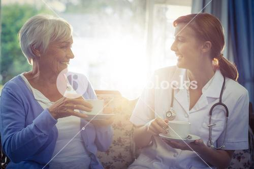Smiling doctor and patient talking while having tea