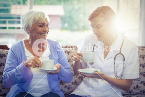 Smiling doctor and patient having tea
