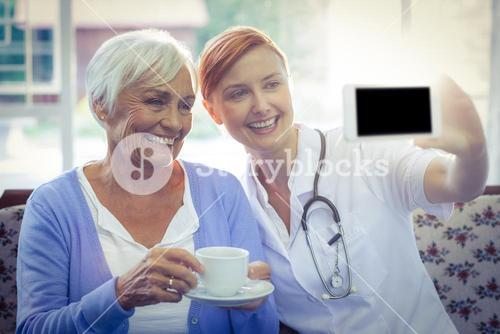 Smiling doctor and patient looking at phone while having tea