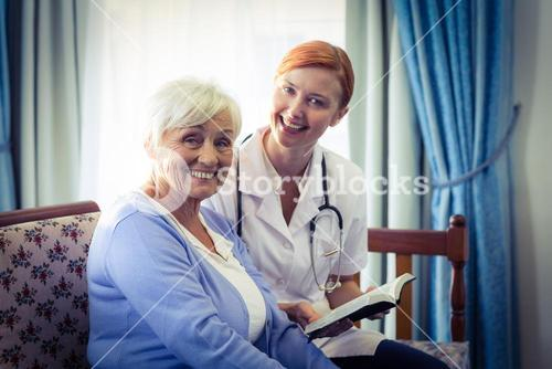 Smiling doctor helping senior woman to read a book