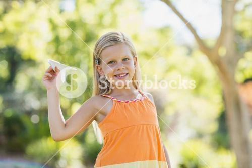 Young girl with a paper plane in park