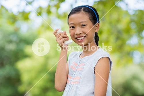 Portrait of girl using an asthma inhaler in the park