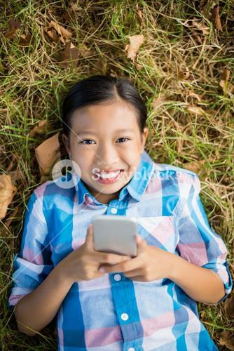 Portrait of smiling Girl lying on grass and using mobile phone