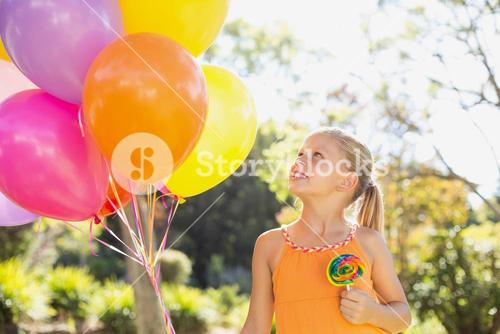 Smiling girl holding balloons and lollypop in the park