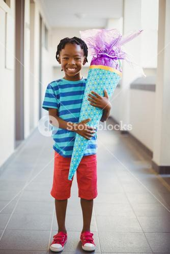 Portrait of smiling schoolboy holding gift in corridor