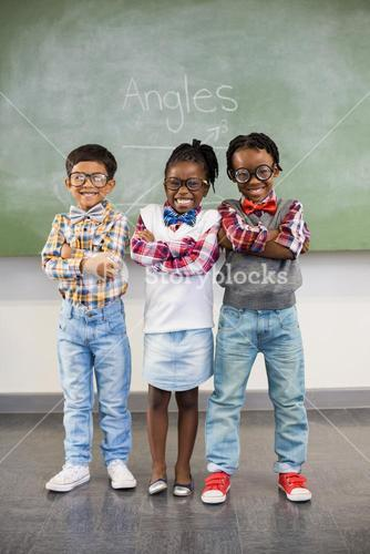 Portrait of three school kids standing with arms crossed against chalkboard