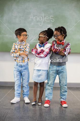 Three school kids talking to each other in classroom