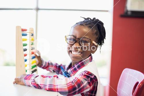 Schoolgirl using a maths abacus at school