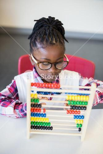 Schoolgirl using a maths abacus in classroom