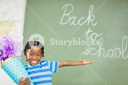 Excited schoolboy holding gift in classroom