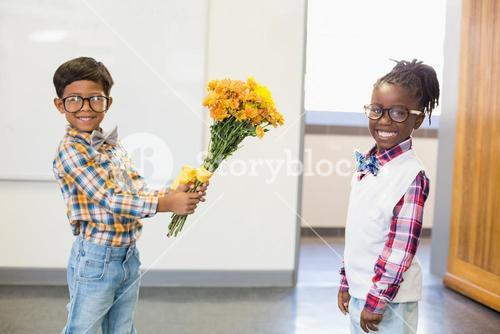 Schoolboy giving a bunch of flowers to a schoolgirl