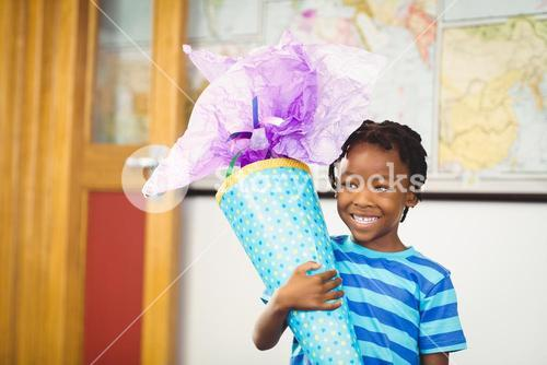 Smiling schoolboy holding gift in classroom