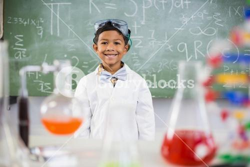 Smiling schoolboy standing in classroom with chemical flask in foreground