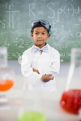 Schoolboy standing in classroom with chemical flask in foreground