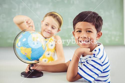 Happy school kids with globe in classroom
