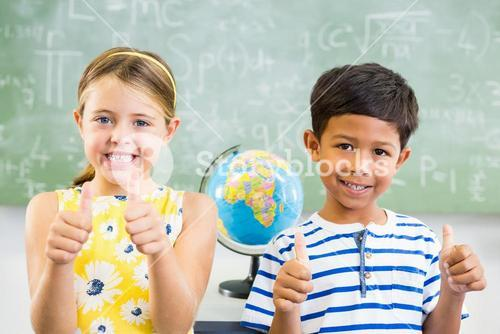 Portrait of smiling school kids showing thumbs up in classroom