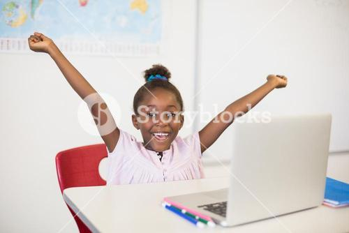 Excited schoolgirl with laptop in classroom