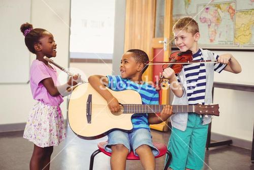 Smiling kids playing guitar, violin, flute in classroom