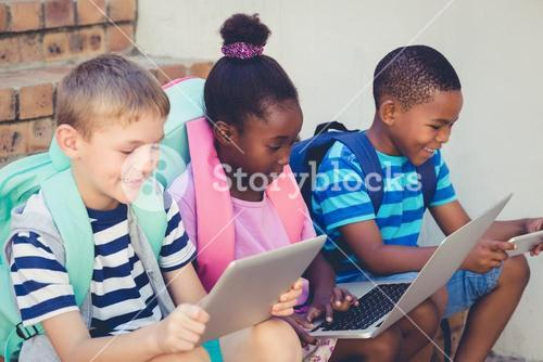 Smiling kids using a laptop and digital tablet on stairs