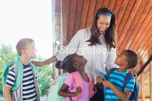 Smiling teacher and kids talking with each other