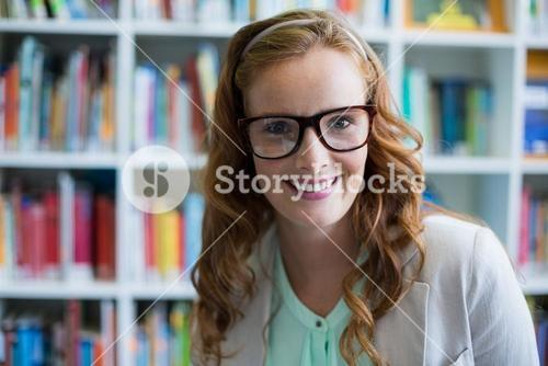 Portrait of smiling school teacher in library