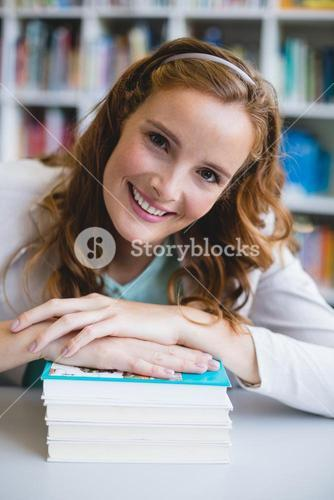 Portrait of smiling school teacher with books in library
