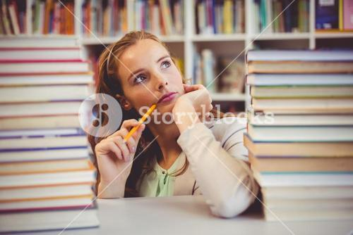 Thoughtful school teacher with books in library