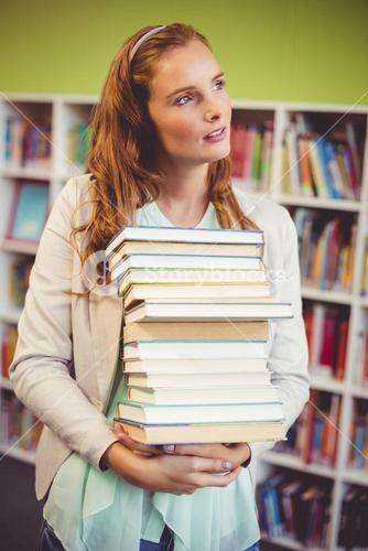 Thoughtful teacher holding a stack of books in library