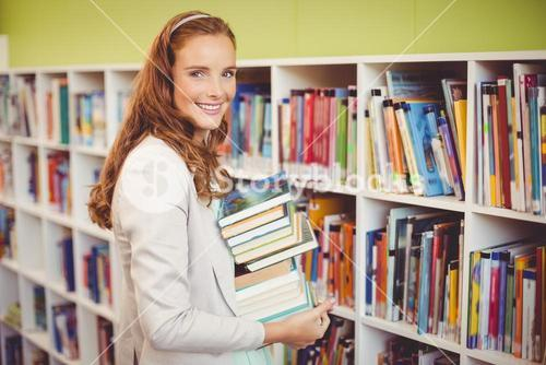 Portrait of smiling teacher holding a stack of books in library