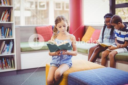 School kids sitting on sofa and reading book in library