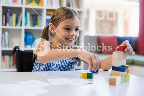 Smiling school girl playing with building block in library