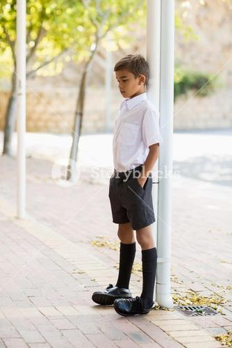 Thoughtful schoolboy leaning on pole with hands in pocket