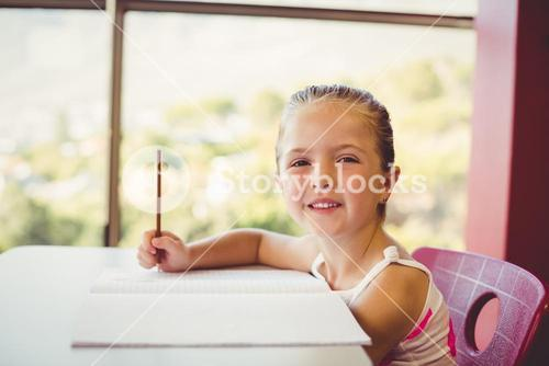 Girl doing homework in classroom